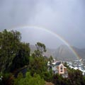 Full rainbow over mountains from house